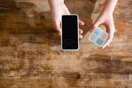 Photo pour Vue du dessus de la femme tenant smartphone avec écran vierge et médicaments dans l'organisateur de pilule - image libre de droit