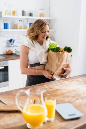 selective focus of woman looking at paper bag with groceries near jug and glass with orange juice