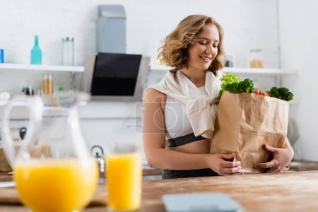 selective focus of young woman looking at paper bag with groceries