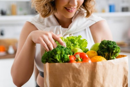 Photo for Cropped view of young woman touching groceries in paper bag - Royalty Free Image