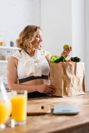 selective focus of woman holding apple near paper bag with vegetables and jug with orange juice