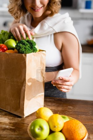 Photo for Cropped view of woman taking selfie with groceries in paper bag - Royalty Free Image