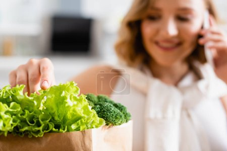 selective focus of woman touching fresh lettuce near broccoli while talking on smartphone
