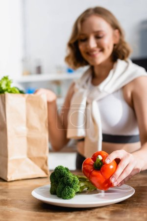 selective focus of woman putting bell pepper on plate near broccoli