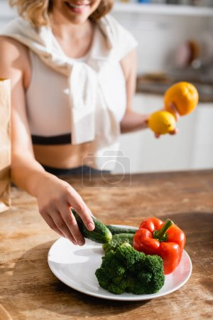 Photo for Cropped view of woman holding cucumber near plate with broccoli and bell pepper - Royalty Free Image