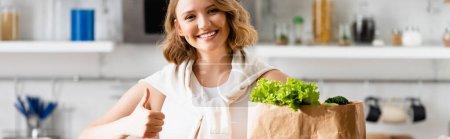 Photo pour Récolte panoramique de femme montrant pouce vers le haut près sac en papier avec laitue - image libre de droit
