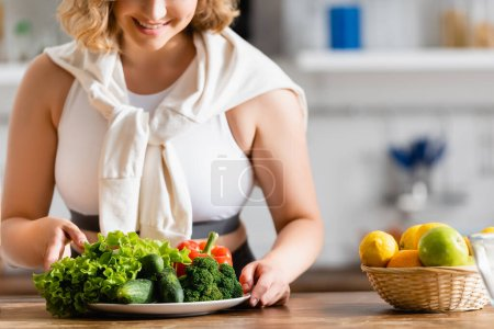 Photo for Cropped view of woman touching plate with vegetables near lemons - Royalty Free Image