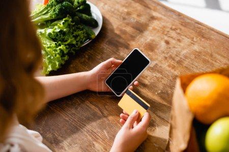 Foto de Vista recortada de la mujer sosteniendo teléfono inteligente con pantalla en blanco y tarjeta de crédito cerca de lechuga y frutas - Imagen libre de derechos