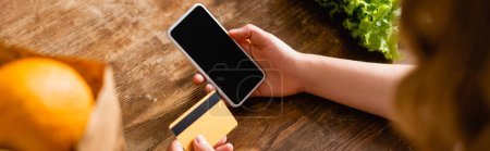 Photo for Panoramic crop of woman holding smartphone with blank screen and credit card near lettuce and orange - Royalty Free Image