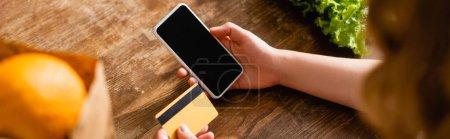 Foto de Cultivo panorámico de mujer sosteniendo teléfono inteligente con pantalla en blanco y tarjeta de crédito cerca de lechuga y naranja - Imagen libre de derechos