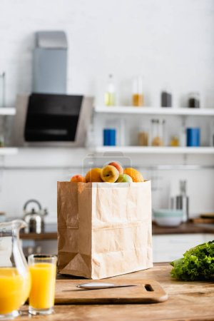Photo for Selective focus of paper bag with groceries near jug with orange juice - Royalty Free Image