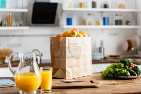 Photo for Selective focus of paper bag with groceries near jug with orange juice on table - Royalty Free Image