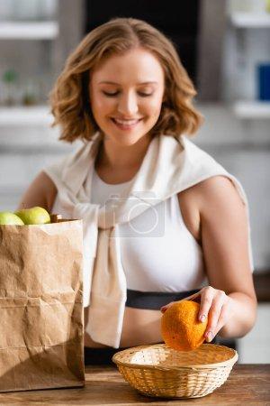 Photo pour Foyer sélectif de la femme tenant orange près du sac en papier avec des fruits - image libre de droit
