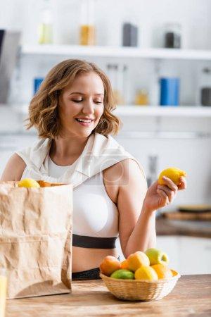 Selektiver Fokus einer jungen Frau mit Zitrone in der Nähe von Papiertüten und Früchten