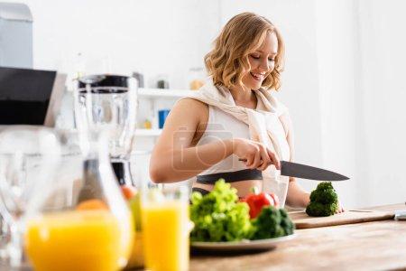 Photo pour Foyer sélectif de femme coupant le brocoli frais sur la planche à découper près de la cruche avec du jus d'orange - image libre de droit