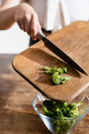 cropped view of woman adding broccoli in bowl