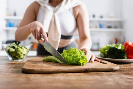 Photo for Cropped view of woman cutting fresh lettuce on chopping board - Royalty Free Image