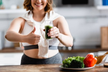 cropped view of young woman holding glass of green smoothie while showing thumb up