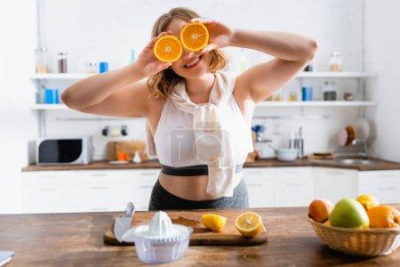 Photo pour Foyer sélectif de la femme couvrant les yeux avec des moitiés d'oranges - image libre de droit