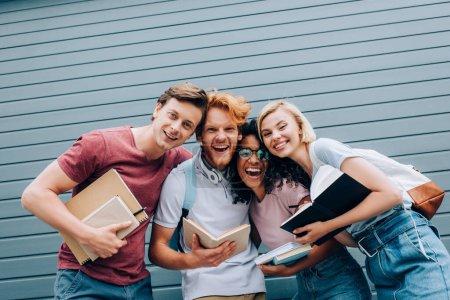 Photo pour Excité étudiants multiculturels regardant caméra tout en tenant des manuels dans la rue - image libre de droit