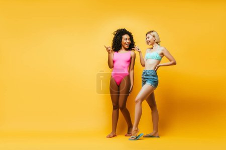 Photo for Full length view of young african american woman and blonde friend with hand on hip pointing with fingers on yellow - Royalty Free Image