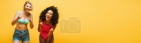 Photo for Horizontal image of excited interracial women laughing and pointing with fingers at camera isolated on yellow - Royalty Free Image