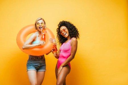 izgatott fajok közötti nők úszás gyűrű és koktél szemüveg pózol sárga