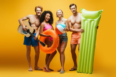 Photo for Full length view of excited multicultural friends with guitar, inflatable mattress, ball and swim ring looking at camera on yellow - Royalty Free Image