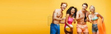Photo pour Image horizontale d'amis multiculturels excités tenant ballon gonflable, anneau de natation et verres à cocktail isolés sur jaune - image libre de droit