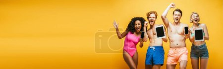 Photo for Horizontal image of excited multicultural friends in summer outfit showing gadgets with blank screen on yellow - Royalty Free Image