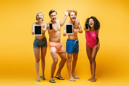 Photo for Full length view of young multiethnic friends in summer outfit showing gadgets with blank screen on yellow - Royalty Free Image
