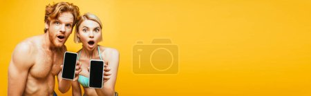 Photo for Horizontal image of shocked blonde woman in swim bra and shirtless man showing smartphones with blank screen isolated on yellow - Royalty Free Image