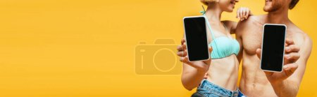 Photo for Cropped view of shirtless man and woman in swim bra showing smartphones with blank screen isolated on yellow, horizontal image - Royalty Free Image