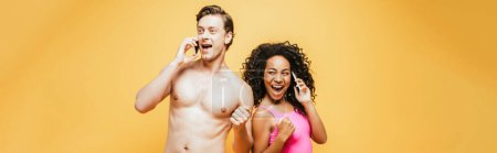 Photo for Horizontal image of excited interracial couple showing winner gesture while talking on smartphones isolated on yellow - Royalty Free Image