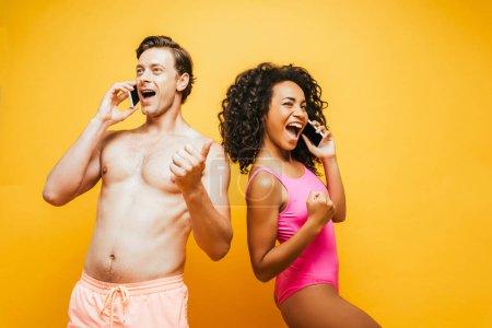 Photo pour Excité couple interracial montrant pouce levé et des gestes gagnants tout en parlant sur les smartphones sur jaune - image libre de droit