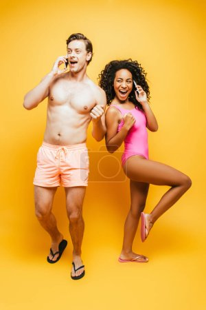 Photo for Excited interracial man and woman showing thumb up and winner gesture while talking on smartphones on yellow - Royalty Free Image