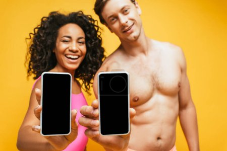 Photo for Selective focus of shirtless man and african american woman showing smartphones with blank screen isolated on yellow - Royalty Free Image