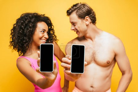 Photo for Curly african american woman and shirtless man looking at each other while showing smartphones with blank screen isolated on yellow - Royalty Free Image