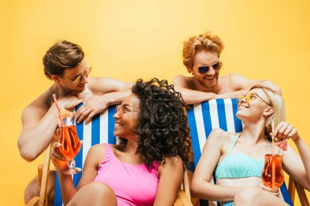 Photo for Multicultural women sitting in deck chairs with cocktails near shirtless men in sunglasses isolated on yellow - Royalty Free Image