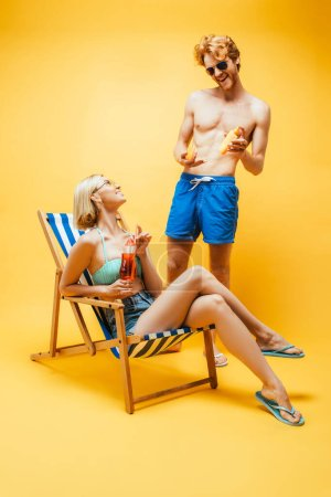 Photo for Young man in blue shorts holding sunscreen near blonde woman sitting in deck chair with cocktail glass on yellow - Royalty Free Image