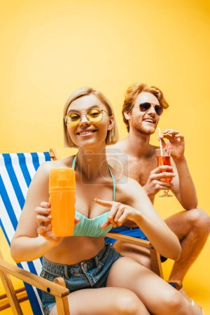 Photo for Blonde woman sitting in deck chair and pointing with finger at orange juice near young man with cocktail glass isolated on yellow - Royalty Free Image