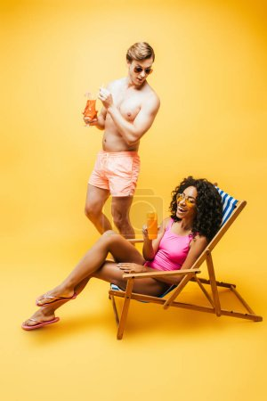 Photo for Young african american woman sitting in deck chair with orange juice near shirtless man with cocktail glass on yellow - Royalty Free Image