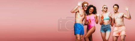 Foto de Imagen horizontal de amigos multiculturales en traje de verano agitando las manos mientras sostiene vasos de cóctel aislados en rosa - Imagen libre de derechos