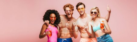 Photo for Horizontal image of excited multicultural friends showing thumbs up while holding cocktail glasses isolated on pink - Royalty Free Image