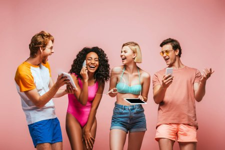 Photo for Excited africal american woman talking on smartphone near multicultural friends using gadgets isolated on pink - Royalty Free Image