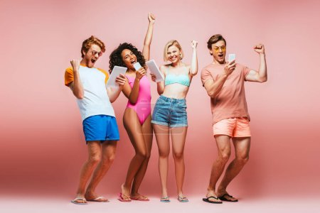 Photo for Full length view of excited multicultural friends in summer outfit showing winner gesture while looking at gadgets on pink - Royalty Free Image