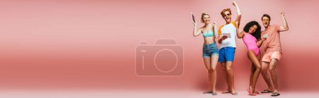 horizontal image of excited multicultural friends in summer outfit showing winner gesture while holding gadgets on pink