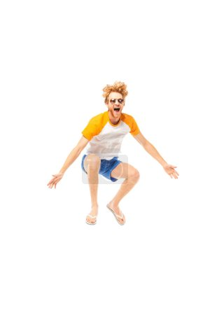 Photo for Excited man in flip flops and sunglasses jumping isolated on white - Royalty Free Image