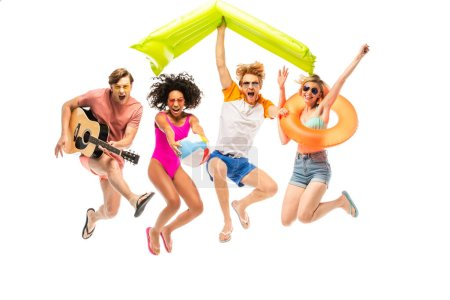 Photo for Excited multiethnic friends with inflatable ball, mattress and acoustic guitar jumping isolated on white - Royalty Free Image