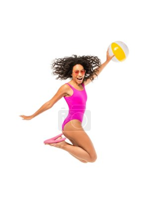 Photo for African american woman in sunglasses and swimsuit holding inflatable ball and jumping isolated on white - Royalty Free Image